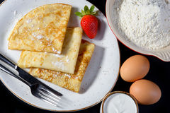 Pancakes on Shrove Tuesday with the ingredients. On a plate on black background with eggs and flour Royalty Free Stock Images