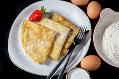 Pancakes on Shrove Tuesday with the ingredients. On a plate on black background with eggs and flour Stock Photography