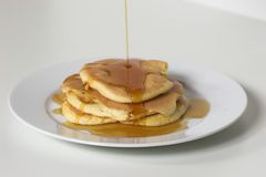 Pancakes and Sirup. Stack of pancakes with syrup being poured on them Stock Image