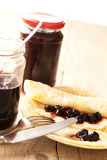 Pancakes with sour cherries jam filling. Rolled pancakes with sour cherries jam filling on a bright background Stock Image