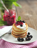 Pancakes with sour cream and black currant jam. On plate royalty free stock images