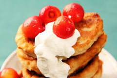 Pancakes with sour cream and a cherry. Royalty Free Stock Image