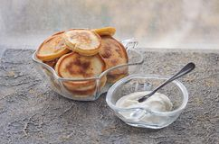 Pancakes with sour cream in glass vases, spoon Royalty Free Stock Photos