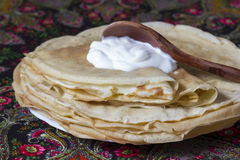 Pancakes with sour cream. The Russian traditional dish, the main thing during  Shrovetide, a symbol of spring and the sun Royalty Free Stock Photography