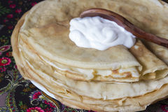 Pancakes with sour cream and a wooden spoon. The Russian traditional dish, the main thing during  Shrovetide, a symbol of spring and the sun Royalty Free Stock Photo