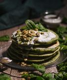 Pancakes with spinach and pumpkin seeds on a wooden table. Count Royalty Free Stock Photos