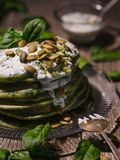 Pancakes with spinach and pumpkin seeds on a wooden table. Count Royalty Free Stock Photo