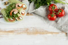Pancakes with spinach and salmon wrapped inside, tomatoes Stock Photo