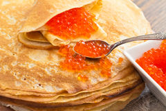 Pancakes with a spoon of red caviar Royalty Free Stock Photography