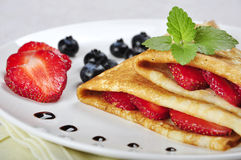 Pancakes with strawberries. Pancakes sereved with strawberries and blueberries on plate Royalty Free Stock Photos