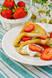 Pancakes with strawberries and basket with berries on a napkin Stock Images