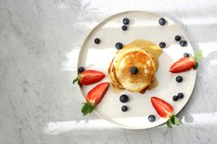 Pancakes with strawberries, blueberries and maple syrup. Sweet breakfast royalty free stock photo
