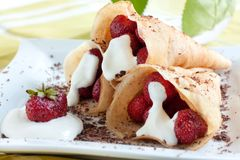 Pancakes with strawberries and cream. Three of them on a white plate Royalty Free Stock Photos