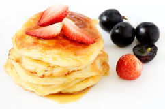 Pancakes with strawberries and grapes Royalty Free Stock Photos