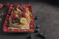 Pancakes with strawberries, raspberries, blueberries, banana, pistachios and syrup on a red plate with white dots. Horizontal. Pancakes with strawberries stock image