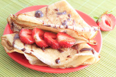 Pancakes with strawberries on red plate. Sweet pancakes with strawberries on red plate royalty free stock images