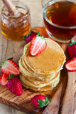 Pancakes with strawberry and honey. Homemade pancakes with ripe strawberry and honey. Selective focus Royalty Free Stock Images