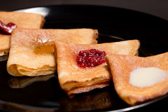 Pancakes with strawberry jam, raspberry jam , sour cream and honey royalty free stock images