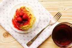 Pancakes with strawberry jam and tea on the wooden table, top vi Royalty Free Stock Photo