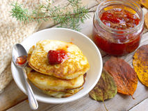 Pancakes and strawberry jam. On the wooden table Stock Image