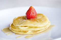 Pancakes and strawberry with maple syrup. On white plate royalty free stock photos