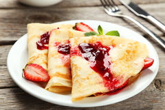 Pancakes with strawberry on plate on grey wooden backgound. Royalty Free Stock Image