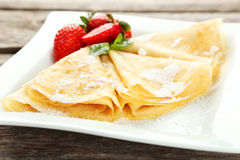 Pancakes with strawberry on plate on grey wooden backgound. Royalty Free Stock Photos