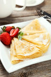 Pancakes with strawberry on plate on grey wooden backgound. Stock Image