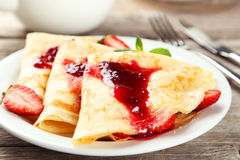 Pancakes with strawberry on plate on grey wooden backgound. Stock Images
