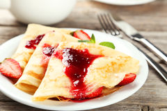 Pancakes with strawberry on plate on a grey wooden backgound Stock Images