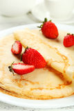 Pancakes with strawberry on plate on white wooden backgound. Royalty Free Stock Image