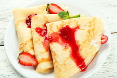 Pancakes with strawberry on plate on white wooden backgound. Stock Photo