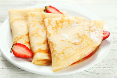 Pancakes with strawberry on plate on white wooden backgound. Stock Images
