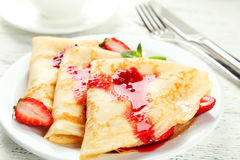 Pancakes with strawberry on plate on white wooden backgound. Stock Photos