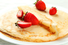 Pancakes with strawberry on plate on white wooden backgound. Royalty Free Stock Photo
