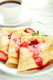 Pancakes with strawberry on plate on white wooden backgound. Royalty Free Stock Photography