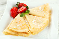 Pancakes with strawberry on plate on a white wooden backgound Royalty Free Stock Images