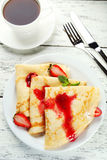 Pancakes with strawberry on plate on a white wooden backgound Stock Photo