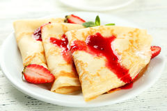 Pancakes with strawberry on plate on a white wooden backgound Stock Photos