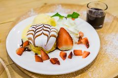 Pancakes with Strawberry and Vanilla Ice cream with chocolate to Royalty Free Stock Images