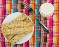 Pancakes with stuffed, fork, glass of milk on checkered napkin Stock Photo
