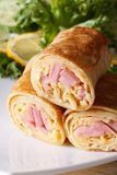 Pancakes stuffed with ham and cheese vertical macro. Pancakes stuffed with ham and cheese on a white plate. vertical macro royalty free stock photo
