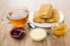 Pancakes with stuffed, jam and condensed milk, cup of tea Royalty Free Stock Images