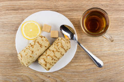 Pancakes with stuffed, lemon, sugar, teaspoon in plate and tea. Pancakes with stuffed, lemon, sugar, teaspoon in plate and cup of tea on wooden table. Top view Stock Photos