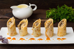 Pancakes stuffed with mushrooms and sour cream on a rustic wooden table. Top view. Close-up stock photos