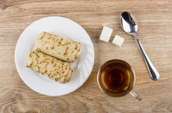 Pancakes with stuffed, sugar, cup of tea and teaspoon. Pancakes with stuffed in plate, sugar, cup of tea and teaspoon on wooden table. Top view Stock Photos