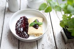 Pancakes stuffed with white cheese with dark fruit jam stock images
