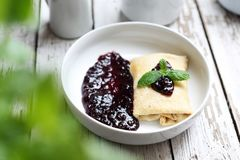 Pancakes stuffed with white cheese with dark fruit jam. Appetite dish. Homemade sweet pancakes, served with cheese stuffing and sweet fruit jam royalty free stock photography