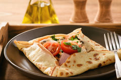 Pancakes sutffed with ham, cheese, tomatoes and mushrooms. Royalty Free Stock Images