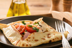 Pancakes sutffed with ham, cheese, tomatoes and mushrooms. Stock Photos